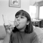 Young asthmatic girl using an inhaler attached to a spacer.