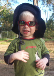 Child with OCA, enjoying the outdoors with sunglasses and hat